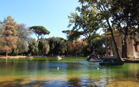 People enjoy  recreational rowing boats in the Villa Borghese public park lake