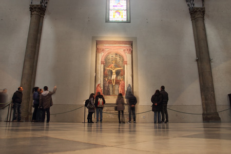 FLORENCE, ITALY - DECEMBER 7, 2014: People admire the famous Holy Trinity fresco by Masaccio 1427 in Santa Maria Novella church Editorial
