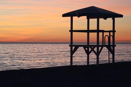 lifeguard tower: Ostia  Beach sunset with lifeguard tower and coastline Stock Photo