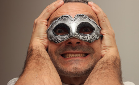 insincere: smiling man at the masquerade with silver mask