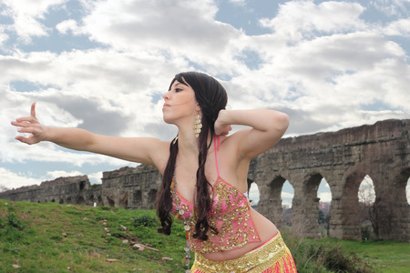 paramour: belly dancer with ancient Roman aqueducts ruins in the background