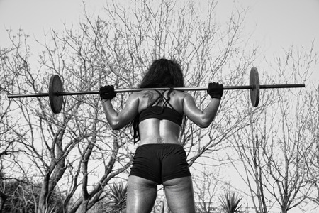 sexy girl: young sporty fitness woman with barbell in the park Stock Photo