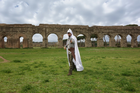 chivalry: Medieval knight under ancient Roman ruins and stormy sky Stock Photo