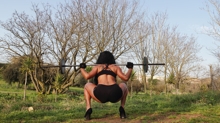 squat: young sporty fitness woman with barbell doing squat Stock Photo