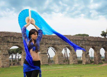 paramour: blue belly dancer under the Roman aqueduct