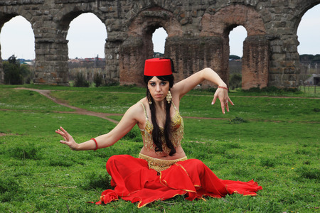 paramour: red hat belly dancer sitting in front of Roman aqueduct ruins