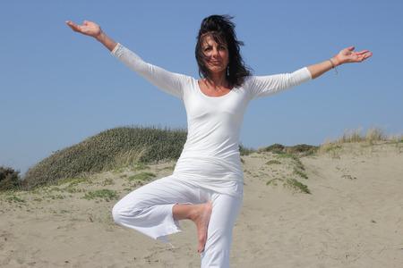 practicing: woman practicing vrksasana yoga posture