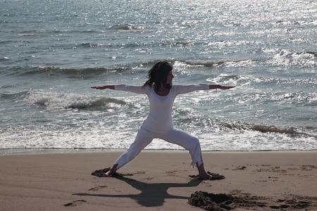 virabhadrasana: woman practicing Virabhadrasana pose on a shore