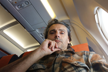 jetsetter: Man on airplane looking at camera Stock Photo