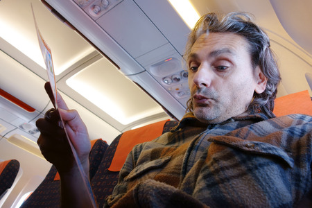 onboard: man on board reading Flight Rules and Safety Precautions