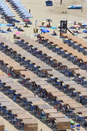 bather: SPERLONGA, ITALY - JULY 11, 2015: People alongside rows of beach huts in the coastal resort of Sperlonga