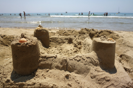the bather: sand castle in Sperlonga beach, unrecognizable blurry people in the background
