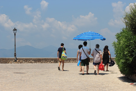 midday: SPERLONGA, ITALY - JULY 12, 2015: People with sun parasol walking under the midday sun along the Tyrrhenian Sea in summer time Editorial