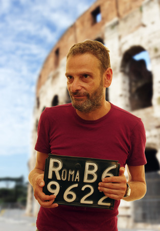 italian man: Italian man with typical car plate in Rome, Italy Stock Photo
