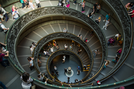 descend: VATICAN CITY, VATICAN STATE - SEPTEMBER 27, 2015: People descend the modern double helix staircase designed by Giuseppe Momo in 1932, Vatican Museums