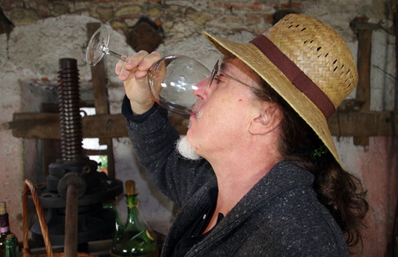 winemaker: Mature winemaker testing wine in old winery