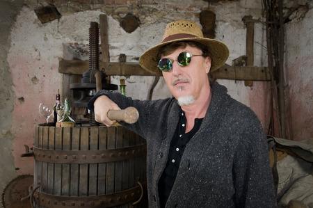 vinery: winemaker next to old press looking at camera