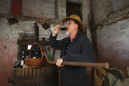 winemaker: Mature winemaker testing wine in old winery
