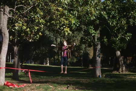 slack: ROME, ITALY - DECEMBER 11, 2015:young man cultivating balance on webbing draped slack between two trees in Villacelimontana Public park Editorial