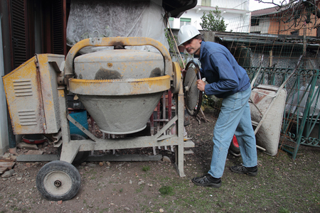 the mixing: Construction Worker Mixing Cement Stock Photo