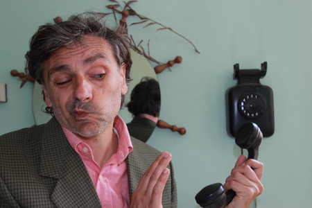 Do not call me, man answering vintage telephone