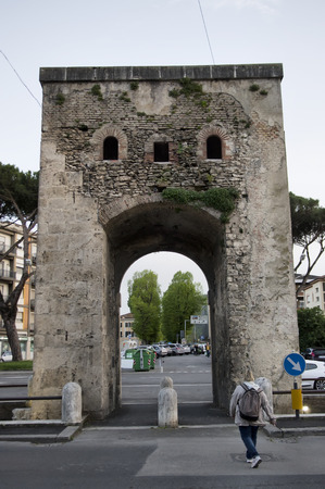 back gate: RIETI, ITALY - APRIL 16: Tourist passes by the ancient Porta Romana this gate dates back to 1586 and was built for Pope Sisto V.