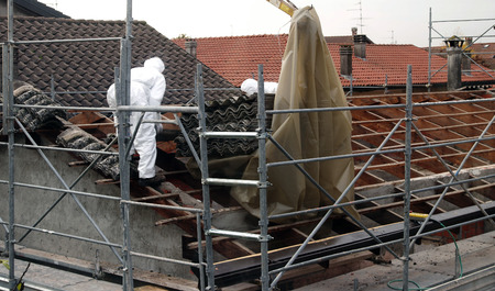 VAPRIO, ITALY -  NOVEMBER 7, 2016: men at work on a roof of an old rural building removing asbestos panels Stock Photo