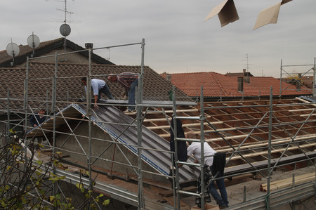 VAPRIO, ITALY -  NOVEMBER 7, 2016: men at work on a roof of ancient rural building