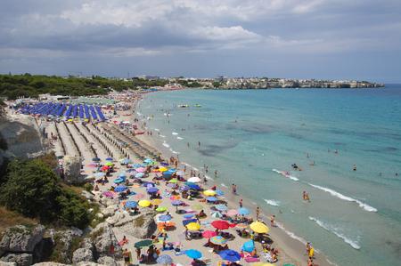 レッチェ, イタリア-7 月 26, 2017: 嵐の前にトッレ・デル・オルソのカラフルなビーチを混雑 報道画像