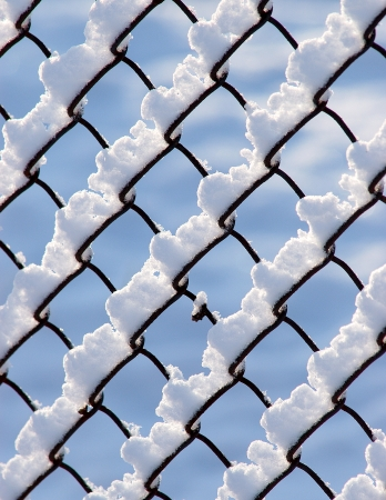 sidelit: Snow piled on the wires of a chain link fence
