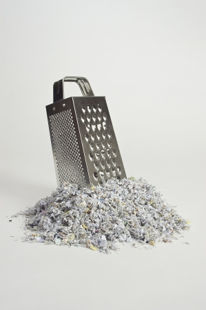 shredding: Cheese grater with paper shreds at the base