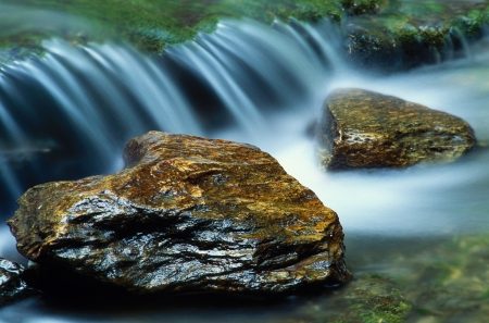A pair of river rocks with a small waterfall