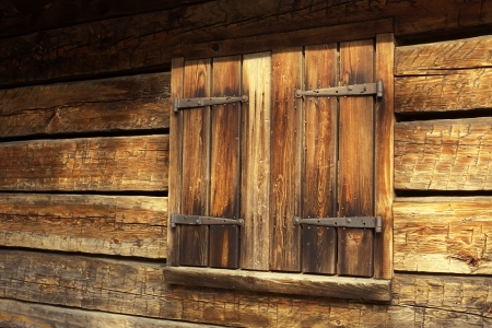 A shuttered window on an old barn