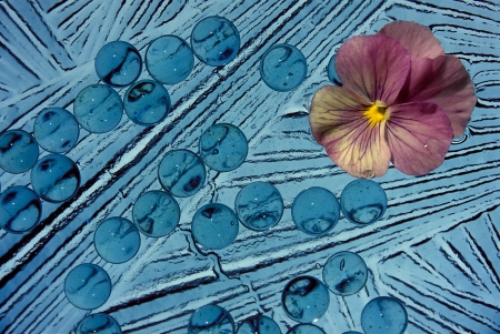 A blue abstract with a pink flower in the upper right corner