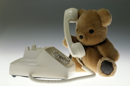 A teddy bear talking on an old white dial phone