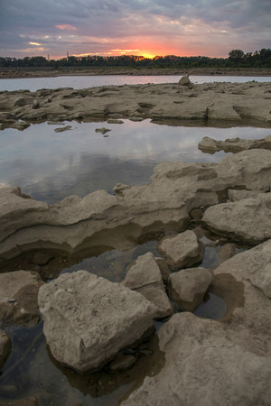 Tide pools and sunset at Falls On The Ohio State Park Stock Photo