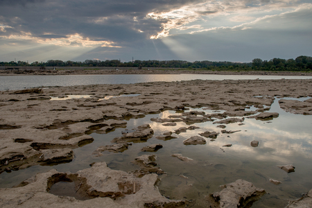 Tide pools and God rays at Falls On The Ohio State Park Stock Photo
