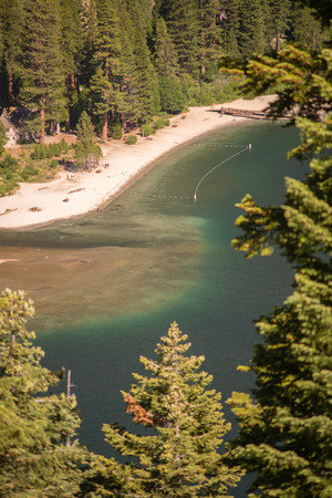 Lake Tahoe through trees with beach area Stock Photo - 74449356