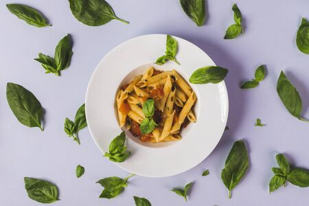 macaroni with basil on a blue background table