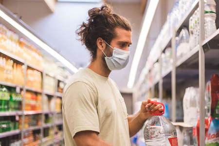young man wearing a medical mask buying on a supermarkert