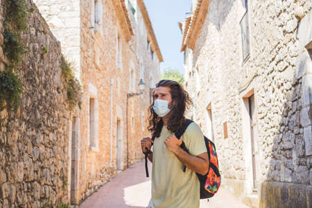 young man walking in a village wearing a face pollution mask to protect himself from the coronavirus