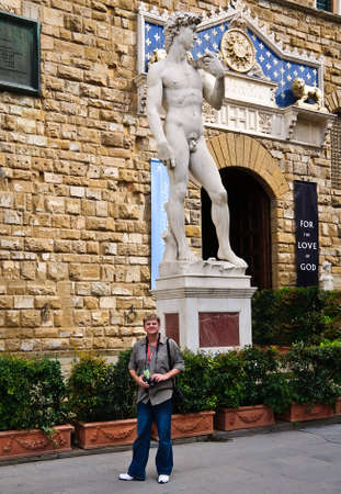 Tourist standing in front of the statue of David by Michelangelo in Florence, Italy