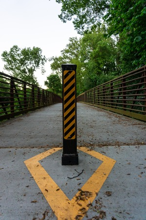 A trail bollard with caution markings on the Atlanta Beltline keeping dangerous vehicles from driving on pedestrian pathway Stock Photo