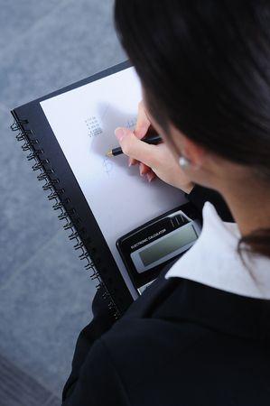 secretarial: businesswoman write and calculate in office; calculator and pen