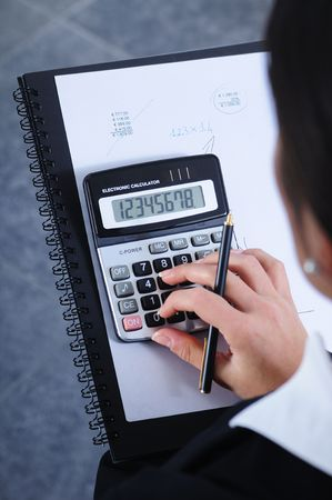 businesswoman write and calculate in office; calculator and pen
