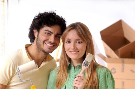 couple in new home with brush for to paint wall