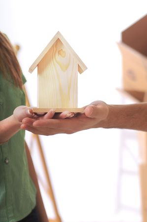 young couple and little home in the hands photo