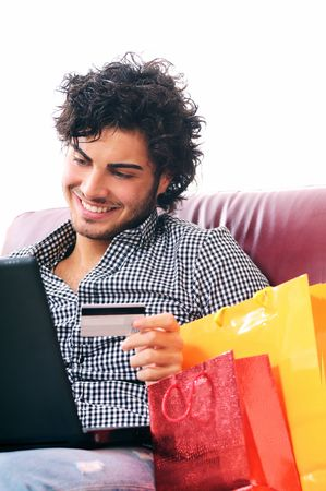shopping man: a young man  using his credit card to purchase over the internet, happiness and amazement