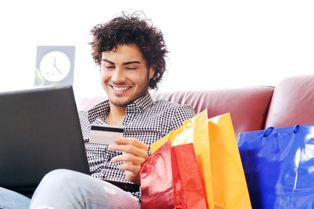 divan sofa: a young man  using his credit card to purchase over the internet, happiness and amazement