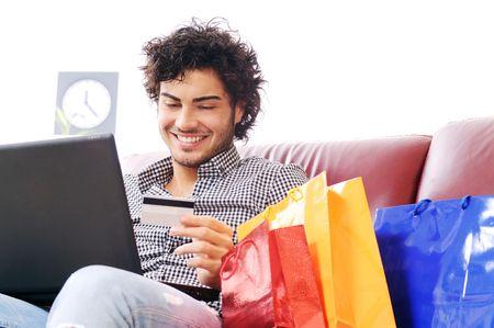 een jonge man met zijn credit card te kopen via het internet, geluk en verwondering